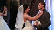 Bride adjusting groom's tie at wedding reception Stock Footage