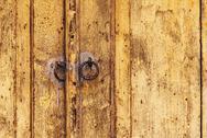 Weathered wooden door with rusty metal knockers Stock Photos