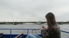Dark-haired woman taking photos of a bridge in St Petersburg. She sits in a Stock Footage