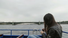 Young brunette woman sightseeing in a river bus. Taking photos on a smartphone Stock Footage
