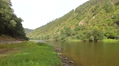 Landscape with calm river with forest mountain rocky shore steady shot 4k Stock Footage