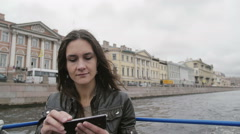 Young woman on a river tour, taking photos, using smartphone. Wind blows hair Stock Footage