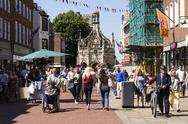 People walk on street in front of the Chichester Cross Stock Photos