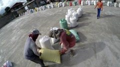 Rice mill workers head carry sack of dried rice Stock Footage