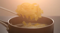 Putting pasta in to the pan with hot water Stock Footage