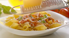 Male hands grating cheese over penne pasta Stock Footage