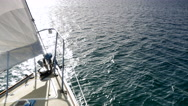 4K Glittering Sun on Sea Sailboat Bow Green Ocean, Boat Deck and Sail Stock Footage