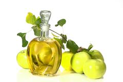 Apple cider vinegar in a glass vessel and green apples Stock Photos