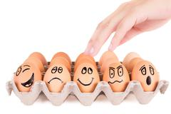 Funny faces painted on brown eggs in a tray Stock Photos