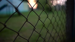 Helpless man's hand shake A Metal Fence Trying To Escape. Sunset infront Stock Footage