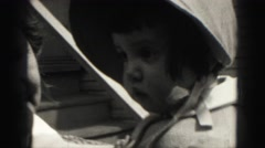 1946: precious baby girl in formal bonnet fashion dress with grandmother Stock Footage