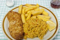 Fish and chips on a plate with savoury rice Stock Photos