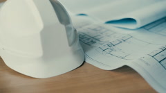 Close Up Slide Shot Of Two Architects Discussing Plan Together At Desk Stock Footage