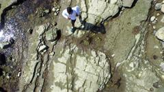 Aerial birds eye view shot of a young man running on a rocky ocean beach shoreli Stock Footage