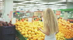 Young woman picking fruit at the market Stock Footage