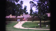 1964: organized marching band coming through the gate down the hill. Stock Footage