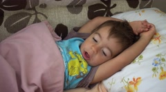 Zoom out sneezing child in bed Stock Footage