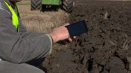 Farmer with tablet PC near moving tractor on field Stock Footage
