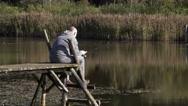 Man sitting on footbridge and fishing Stock Footage