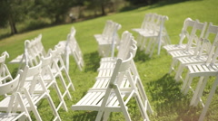Rows of arranged white empty chairs on a green grass Stock Footage