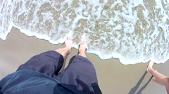 Ocean tide rushing over pasty white feet. Stock Footage