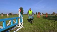 Horse handler with wheelbarrow on hurdle field Stock Footage