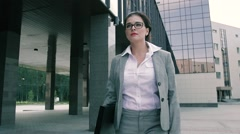 Portrait of beautiful business woman walking confidently to the office building Stock Footage