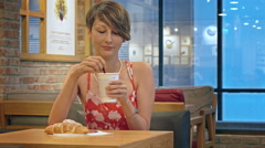 Pretty girl with short brunette hair in red dress drinks coffee with croissant. Stock Footage