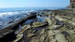 Tracking shot of a young man running on a rocky ocean beach shoreline. Stock Footage