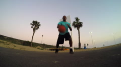 A young man playing basketball on a court at the beach as the sun sets. Stock Footage