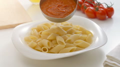 Putting tomato sauce on penne pasta Stock Footage