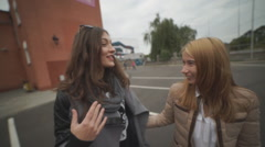 Two happy young girls gossiping and laughing Stock Footage