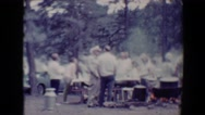1967: large group of people gathered in park, cooking and listening to music Stock Footage