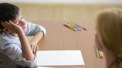 Young boy sitting in silence during session with young psychologist. Stock Footage