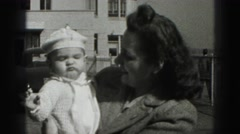 1946: mommy cuddling her baby with the smile on street side. HARRISBURG Stock Footage