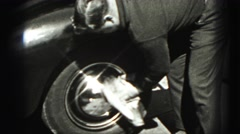 1946: man leaning on car as he polishes the hubcap HARRISBURG Stock Footage