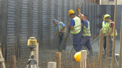 Construction workers concreting at building place, wide angle by Sheyno. Stock Footage