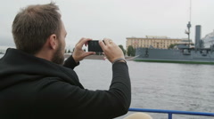 A man is sightseeing. Taking photos of the cruiser Aurora in St Petersburg Stock Footage