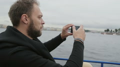 Sideview of a handsome man taking photos while sightseeing in St Petersburg Stock Footage