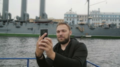 Happy handsome man has great time sightseeing. Taking selfie in front of Cruiser Stock Footage