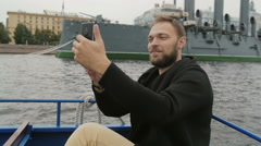 Happy handsome man sightseeing in St Petersburg. Taking selfie in front of Stock Footage
