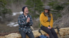 A man and woman getting ready to hike together after resting on a fallen tree tr Stock Footage