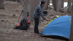 Couple camping in the woods. Man is a gentleman and helps woman get out of tent. Stock Footage