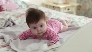 Portrait of young infants lying on his stomach and looking at the camera Stock Footage