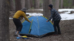 A man and woman couple packing up tent and campsite together. Stock Footage