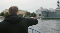 Sightseeing in St Petersburg. Man uses smartphone, takes photos of the Cruiser Stock Footage