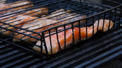 Fillet of red fish (salmon, trout) on the grill, close-up Stock Footage
