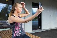 Beautiful Woman In Sportswear Taking Selfie While Sitting On Ben Stock Photos