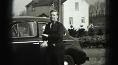 1946: father arriving home stops to open the hood of the car and check the belt Stock Footage
