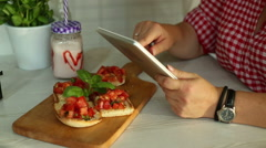 Close-Up of female hands typing on touch screen of digital tablet in restaurant Stock Footage